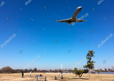 """Stock Picture of People watch a commercial passenger jet fly over Gravelly Point Park as it comes in to land at Ronald Reagan Washington National Airport in Arlington, Va., across the Potomac River from the nation's capital. In one of Virginia's most liberal jurisdictions, political leaders are just saying 'no' to a proposal in Congress to name a popular park for former first lady Nancy Reagan. Legislation passed a House committee last month to rename Gravelly Point Park, which sits on federal land adjacent to Ronald Reagan National Airport, for the former first lady. The bill's sponsor, Georgia Republican Jody Hice, says the change """"would be a fitting tribute, given its proximity to Reagan National Airport."""" The proposal, though, is not supported by political leaders in Arlington County, where the park is located"""