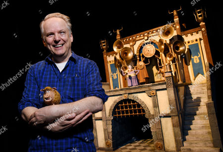 """Nick Park, director of the stop-motion animated film """"Early Man,"""" and the voice of the wild boar character Hognob, cradles the puppet as he poses in front of the film's Royal Box set at the Beverly Hilton in Beverly Hills, Calif. The film opens nationwide on Friday, Feb. 16"""