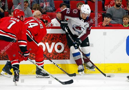Gabriel Landeskog, Justin Williams, Derek Ryan. Colorado Avalanche's Gabriel Landeskog (92) looks to pass the puck in front of the oncoming Carolina Hurricanes' Justin Williams (14) and Derek Ryan (7) during the first period of an NHL hockey game, in Raleigh, N.C