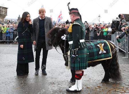 Prince Harry and Meghan Markle meet Pony Major Mark Wilkinson and regimental mascot Cruachan IV during a walkabout on the esplanade at Edinburgh Castle, during their visit to Scotland.