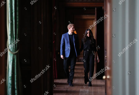 Prince Harry and Meghan Markle walk through the corridors of the Palace of Holyroodhouse on their way to a reception for young people at the Palace, in Edinburgh, during their visit to Scotland.