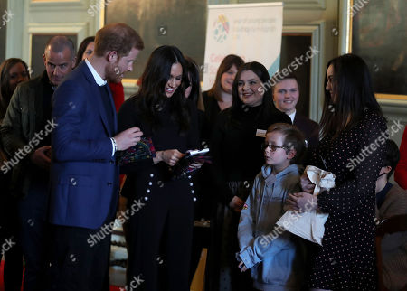 Prince Harry and Meghan Markle receive gifts during a reception for young people at the Palace of Holyroodhouse, in Edinburgh, during their visit to Scotland.