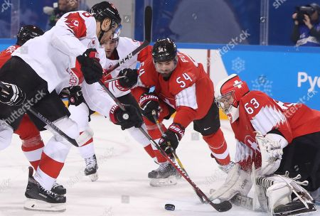 Wojtek Wolski (L) of Canada in action against goalie Leonardo Genoni (R) and Philippe Furrer of Switzerland during the men's Ice Hockey preliminary round match between Switzerland and Canada at the Kwandong Hockey Centre in Gangneung during the PyeongChang Winter Olympic Games 2018, South Korea, 15 February 2018.