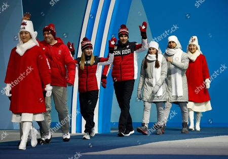 Curling mixed doubles gold medalists Kaitlyn Lawes, third from left, and John Morris, fourth from left, of Canada, wave as they are followed by bronze medalists Anastasia Bryzgalova and Aleksandr Krushelnitckii, from Russia, during their medals ceremony at the 2018 Winter Olympics in Pyeongchang, South Korea