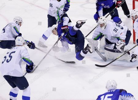 Goaltender Gasper Kroselj (32), of Slovenia, watches as Troy Terry (23), of the United States, falls to the ice during the third period of the preliminary round of the men's hockey game at the 2018 Winter Olympics in Gangneung, South Korea, . Slovenia won 3-2