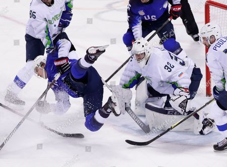 Goaltender Gasper Kroselj (32), of Slovenia, watches as Troy Terry (23), of the United States, falls to the ice during the third period of the preliminary round of the men's hockey game at the 2018 Winter Olympics in Gangneung, South Korea