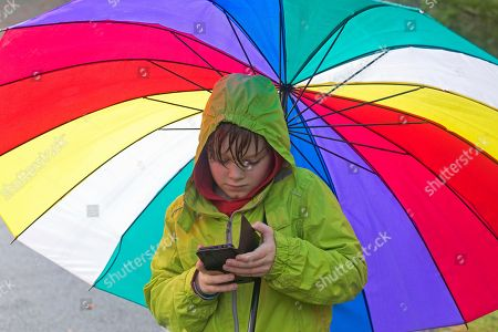 MODEL RELEASED Boy with Smartphone under a large colorful umbrella, Germany