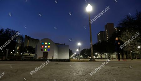 """Stock Picture of A woman passes Ellsworth Kelly's """"Austin"""" at the Blanton Museum of Art, in Austin, Texas. The exhibit, a 2,715-square-foot stone building with luminous colored glass windows is set to open to the public Sunday"""