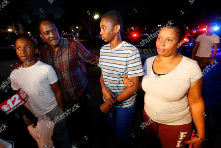 Max Charles, second from right, 14, a student at Marjory Stoneman Douglas High School in Parkland, Fla., speaks to members of the media after being picked up by family members at a nearby hotel, in Coral Springs, Fla. A former student opened fire at the Florida high school Wednesday, killing more than a dozen people and sending scores of students fleeing into the streets in the nation's deadliest school shooting since a gunman attacked an elementary school in Newtown, Connecticut