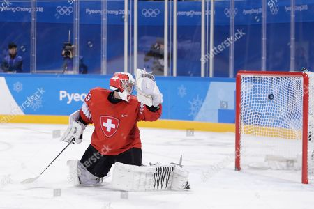 Switzerland goalkeeper Leonardo Genoni watches as a shot by Wojtek Wolski (8), of Canada, enters his net for a goal during the second period of a preliminary round men's hockey game at the 2018 Winter Olympics in Gangneung, South Korea