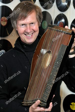 Stock Image of Third Man Museum owner Gerhard Strassgschwandtner with the zither on which Anton Karas played the film score