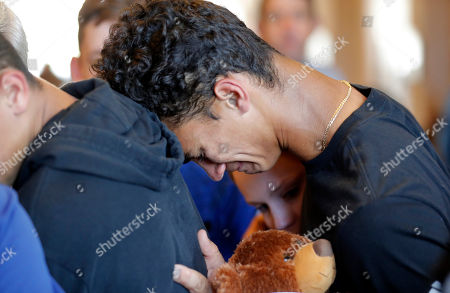 Austin Burden, 17, cries on the shoulder of a friend after a vigil at the Parkland Baptist Church, for the victims of the Wednesday shooting at Marjory Stoneman Douglas High School, in Parkland, Fla., . Nikolas Cruz, a former student, was charged with 17 counts of premeditated murder on Thursday