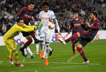 Marseille goalkeeper Yohann Pele, left, saves a goal as Braga's Paulinho, right, kicks the ball during their Europa League round of 32 first leg soccer match at the Velodrome stadium in Marseille, Thursday, Feb.15, 2018