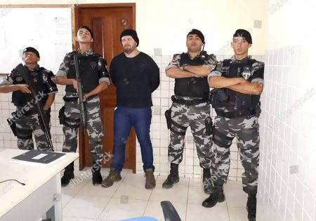This late photo released by the Military Police press office in Brazil's Para state, shows military police standing with who they identify as Jose Irandir Cardoso at a police station in Breves, Para state, Brazil. The man convicted in the killing of yachtsman Sir Peter Blake was caught after being on the run for more than 15 years