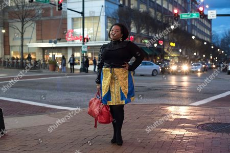 Nicole Moore dressed in Wakanda-inspired attire poses for a portrait before seeing Black Panther in Silver Spring, Md