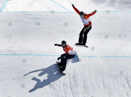 Lindsey Jacobellis, of the United States, left and Tess Critchlow, of Canada, run the course during the women's snowboard cross quarterfinals at Phoenix Snow Park at the 2018 Winter Olympics in Pyeongchang, South Korea