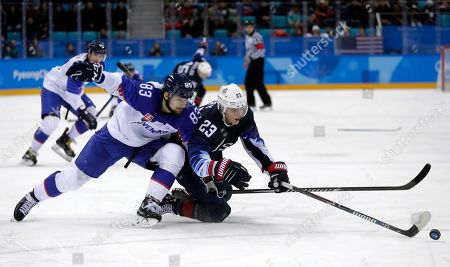 Peter Olvecky (85), of Slovakia, and Troy Terry (23), of the United States, battle for the puck during the second period of the preliminary round of the men's hockey game at the 2018 Winter Olympics in Gangneung, South Korea