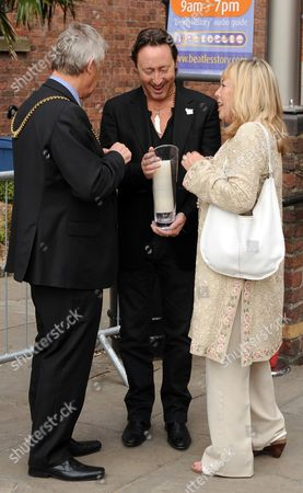 Julian Lennon and mother Cynthia Lennon lighting a white candle for peace outside the Beatles story in Liverpool