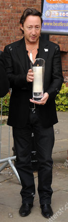 Julian Lennon lighting a white candle for peace outside the Beatles story in Liverpool