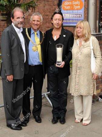 Julian Lennon and mother Cynthia Lennon ighting a white candle for peace outside the Beatles story in Liverpool
