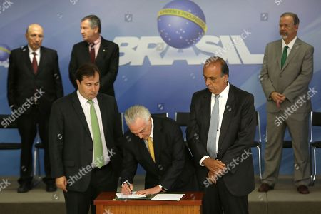 Michel Temer, Rodrigo Maia, Luiz Fernando Pezao. Brazil's President Michel Temer, center, accompanied by the President of the Chamber of Deputies Rodrigo Maia, left, and Governor of Rio de Janeiro Luiz Fernando Pezao, right, signs the decree for the military intervention of Rio de Janeiro's local police, at the Planalto Presidential Palace, in Brasilia, Brazil, . Brazil's federal government issued a decree Friday to put the military in charge of Rio de Janeiro's local police amid a spike in violence