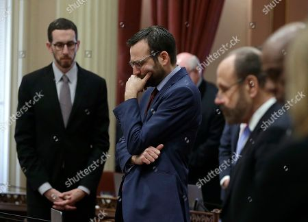 Democratic State Sen. Ben Allen, of Santa Monica, second from left, and other members of the California state Senate, bow their heads during a moment of silence in remembrance the 17 people killed in the Florida school shooting, in Sacramento, Calif