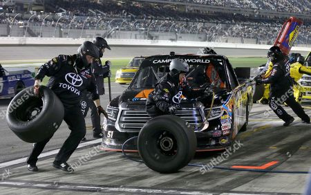Crew member perform a pit stop on driver Spencer Davis' truck during the NASCAR Truck Series auto race at Daytona International Speedway in Daytona Beach, Fla
