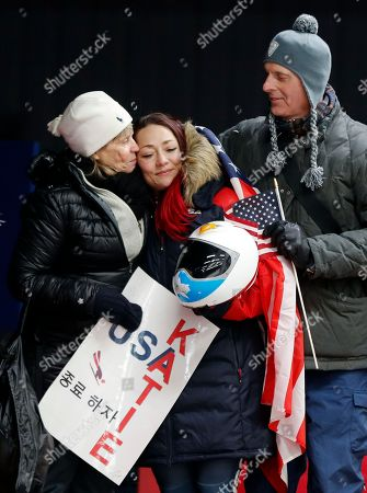 Stock Image of Katie Uhlaender of United States, center, is hugged and kissed by Jean Schaefer, left, and Dr. Brian Boxer Wachler in the finish area after the final run of the women's skeleton competition at the 2018 Winter Olympics in Pyeongchang, South Korea, . Schaefer is the mother of deceased American bobsledder Steve Holcomb and Wachler is a Holcomb family friend and doctor. They came to support Uhlaender, who was friends with Holcomb