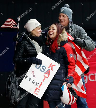 Katie Uhlaender of United States, center, is hugged and kissed by Jean Schaefer, left, and Dr. Brian Boxer Wachler in the finish area after the final run of the women's skeleton competition at the 2018 Winter Olympics in Pyeongchang, South Korea, . Schaefer is the mother of deceased American bobsledder Steve Holcomb and Wachler is a Holcomb family friend and doctor. They came to support Uhlaender, who was friends with Holcomb