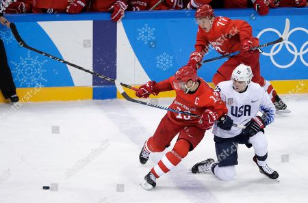 Russian athlete Pavel Datsyuk (13) battles with Troy Terry (23), of the United States, for the puck during the third period of the preliminary round of the men's hockey game at the 2018 Winter Olympics in Gangneung, South Korea