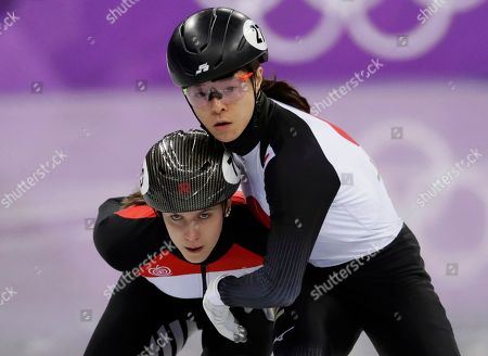 Sumire Kikuchi, right, of Japan and Sara Bacskai of Hungary collide during their women's 1500 meters short track speedskating heat in the Gangneung Ice Arena at the 2018 Winter Olympics in Gangneung, South Korea