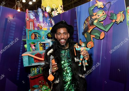 Brandon Mychal Smith, the voice of Michelangelo in Nickelodeon's brand-new animated series Rise of the Teenage Mutant Ninja Turtles, shows off the all-new Michelangelo action figure from Playmates Toys during the North American International Toy Fair in New York