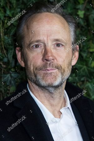 Stock Image of John Benjamin Hickey poses for photographers upon arrival at the Charles Finch and Chanel pre Bafta party in London