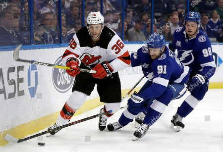 Nick Lappin, Steven Stamkos, Mikhail Sergachev. New Jersey Devils' Nick Lappin (36) and Tampa Bay Lightning center Steven Stamkos (91) chase a loose puck during the first period of an NHL hockey game, in Tampa, Fla. Trailing the play is Lightning's defenseman Mikhail Sergachev (98