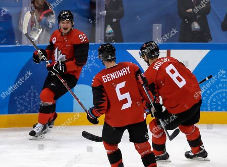 Christian Thomas (92), of Canada, celebrates with Chay Genoway (5) and Wojtek Wolski (8) after scoring a goal against South Korea during the first period of the preliminary round of the men's hockey game at the 2018 Winter Olympics in Gangneung, South Korea