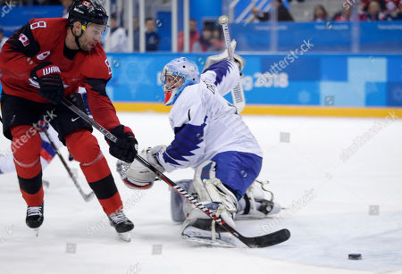 Wojtek Wolski (8), of Canada, tries to take a shot around goalie Matt Dalton (1), of South Korea, during the first period of the preliminary round of the men's hockey game at the 2018 Winter Olympics in Gangneung, South Korea