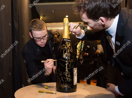 Will Poulter and Edward Holcroft sign a Taittinger bottle