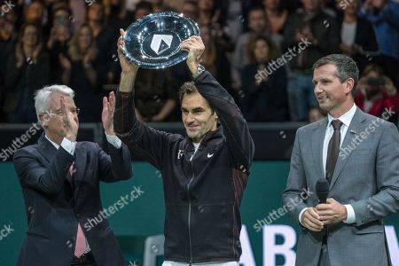 Roger Federer of Switzerland holds up the trophy as he celebrates winning his match against Bulgaria's Grigor Dimitrov in two sets, 6-2, 6-2, in the men's singles final of the ABN AMRO world tennis tournament at the Ahoy stadium in Rotterdam, Netherlands, . At right is tournament director Richard Krajicek