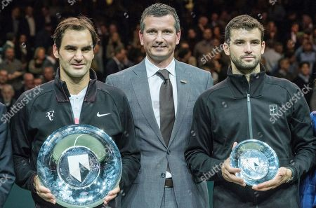 Roger Federer, left, of Switzerland holds the trophy as he celebrates winning his match against Bulgaria's Grigor Dimitrov, right, in two sets, 6-2, 6-2, in the men's singles final of the ABN AMRO world tennis tournament at the Ahoy stadium in Rotterdam, Netherlands, . At center is tournament director Richard Krajicek