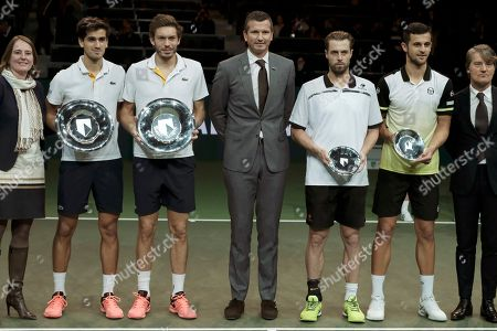At left, Pierre-Hugues Herbert of France and Nicolas Mahut of France celebrate with their trophies after winning the final match against Ivan Dodig of Croatia and Rajeev Ram of the US, at right, in the men's doubles final of the ABN AMRO world tennis tournament at the Ahoy stadium in Rotterdam, Netherlands, . At center is tournament director Richard Krajicek