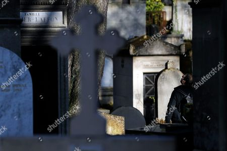 A visitor walks among the graves of the Pere Lachaise cemetery in Paris, France, 18 February 2018.  The Cemetery of 45 hectares and around 70000 plots is the most famous necropolis in France and the most visited by tourists with more than three millions visitors per year. Honore de Balzac, Oscar Wilde, Maria Callas, Frederic Chopin, Marcel Proust, Jim Morrison and many other famous artists were burried in this cemetery.