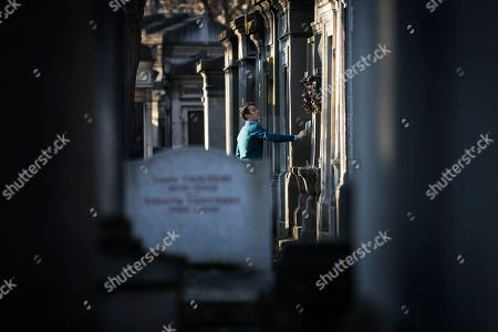 A man cleans a vault in the Pere Lachaise cemetery in Paris, France, 18 February 2018. The Cemetery of 45 hectares and around 70000 plots is the most famous necropolis in France and the most visited by tourists with more than three millions visitors per year. Honore de Balzac, Oscar Wilde, Maria Callas, Frederic Chopin, Marcel Proust, Jim Morrison and many other famous artists were burried in this cemetery.