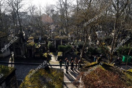 A guide leads visitors among the graves of the Pere Lachaise cemetery in Paris, France, 18 February 2018. The Cemetery of 45 hectares and around 70000 plots is the most famous necropolis in France and the most visited by tourists with more than three millions visitors per year. Honore de Balzac, Oscar Wilde, Maria Callas, Frederic Chopin, Marcel Proust, Jim Morrison and many other famous artists were burried in this cemetery.