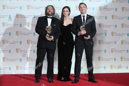 Stock Image of Paul Machliss, Jonathan Amos, Hayley Squires. Paul Machliss, left, and Jonathan Amos, right, hold their awards for Editing for 'Baby Driver' as they pose for photographers with actress Hayley Squires backstage at the BAFTA 2018 Awards in London