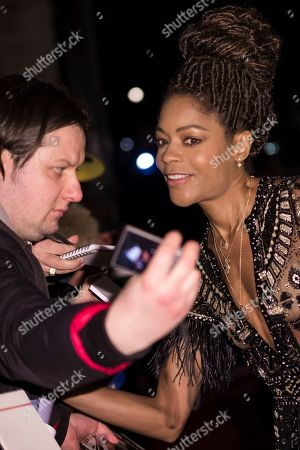 Naomi Harris takes a picture with a fan upon arrival at the BAFTA Film Awards after-party, in London