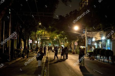 People, who fled their buildings after an earthquake alarm sounded, stand in a street in the Roma Norte neighborhood in Mexico City, in the early morning hours of . For the second time in days, the earthquake alarm sounded in the capital, giving residents a short window to exit buildings before they began to sway
