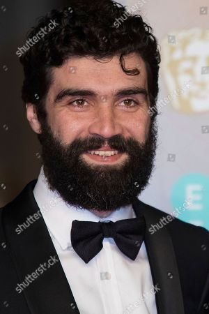 Stock Photo of Alec Secareanu poses for photographers upon arrival at the BAFTA Awards 2018 in London