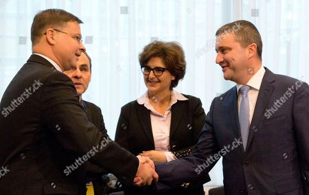 European Commissioner for Euro and Social Dialogue Valdis Dombrovkis, left, shakes hands with Bulgarian Finance Minister Vladislav Goranov during a macroeconomic dialogue with social partners at the EU Council building in Brussels on