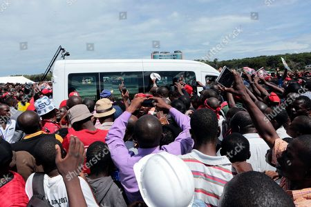Movement for Democtratic Change supporters rush to catch a glimpse of the vehicle carrying the coffin of their party leader, Morgan Tsvangirai in Harare, Monday, Feb, 19, 2018. Zimbabwes veteran opposition leader Morgan Tsvangirai died on Feb 14 aged 65, bringing an end to his long campaign to lead the country. Interim party President Nelson Chamisa said the party would win the elections scheduled for later this year as a tribute to the deceased leader