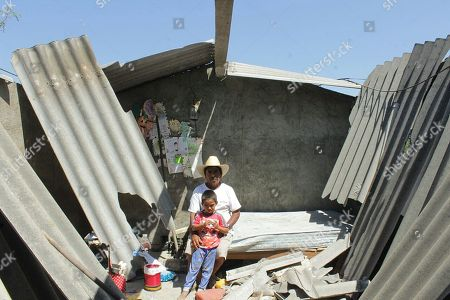 People pose amid the debris of their earthquake damaged home in Jamiltepec, Mexico, 19 February 2019. The country is assessing the damage caused by a 7.2 earthquake that struck Mexico on 16 February. At least 200 homes have been at least partially destroyed and power has been cut off for 1.3 million residents in the affected areas.